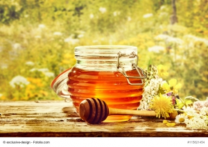 Bowl of honey with dipper in field of flowers